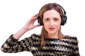 Beautiful woman standing listening to music on black headphones, isolated on white, studio shot — Stock Photo