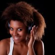 Beautiful black woman happy listening music in headphones, isolated on black background. Studio shot. — Stock Photo #9835308