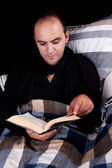 Man lying on the sofa reading a book, isolated on black, studio shot. — Stock Photo