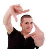 A young man framing his face with his hands, isolated on white, studio shot — Stock Photo