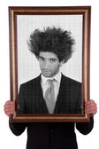 Man holding a decorative frame and standing inside it on black and white, isolated on white, studio shot — Stock Photo