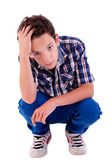 Young man squatting, worried, isolated on white background studio shot — Stock Photo