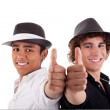 Two young man of different colors, with thumb up and a hat, isolated on white, studio shot — Stock Photo