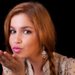 Pretty young caucasian girl sending kiss, with golden reflexion, isolated on black, studio shot — Stock Photo