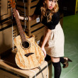 Stock Photo: Beautiful young womwith classical guitar in warehouse with boxes like scenario