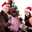 Happy young couple, opening gifts beside Christmas tree, isolated on white — Stock Photo