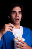 Young man, with popcorn watching — Stockfoto