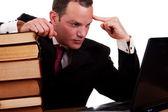 Biznesmen na biurko z książek, patrząc na komputerze, na białym tle na białym tle, łapka. — Zdjęcie stockowe