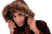 Portrait of a young man with a furry hood , in autumn and winter clothes, isolated on white. Studio shot — Stock Photo