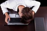 Cansado de jovem empresário com a cabeça no computador em um fundo preto. estúdio tiro — Fotografia Stock