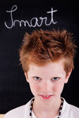 Cute and smart kid, in front of blackboard — Stock Photo