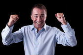 Portrait of a very happy businessman with his arms raised, on black background. Studio shot — Stock Photo