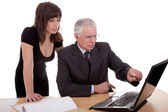 Businessman and woman discussing, because of work, pointing to computer, isolated on white background — Stock Photo
