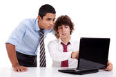 Two young businessmen working together on a laptop, isolated on white, studio shot — Photo