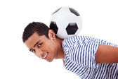 Handsome latin boy holding a soccer ball, isolated on white, studio shot — ストック写真