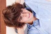 Young man, lying on the couch. Studio shot. — Stock Photo