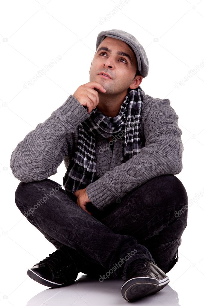 Portrait of a young man sitting on the floor, thinking and looking up, in autumn and winter clothes, isolated on white, Studio shot  Stock Photo #9896609