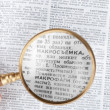 Magnifying glass enlarging text — Stock Photo