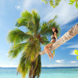 Fashion woman siting upon palm tree on the beach — Stock Photo #10235707