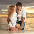 Young couple on the sea sunset background — Stok fotoğraf