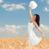 Young woman in the field of golden wheat — Stock Photo