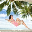Happy woman relaxing in hammock on a tropical beach — Stock Photo #10723886