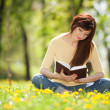 Young woman reading a book in the park with flowers — Stok fotoğraf