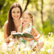 Mother and daughter drawing on grass in park — Stock Photo #10723965