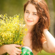 Stock Photo: Young redhead woman in the park with flowers