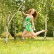 Young redhead woman jumping in the park with flowers — Stock Photo