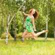 Stock Photo: Young redhead woman jumping in the park with flowers