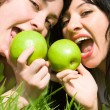 Pretty women eating green apples on the summer glade - Stock Photo