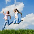 Two happy women jumping on the green grass — Stock fotografie