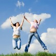 Two happy women jumping on the green grass — Stock Photo #9247506