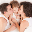 Happy family, mother, father and daughter on the white bed — Stock Photo