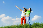 Two young women on a green meadow — Stock Photo