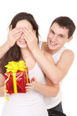 Young man presents gift to woman, on white background — Stock Photo
