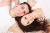 Young happy couple lying in the white bed — Stock Photo