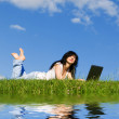 Pretty woman with laptop on the green grass — 图库照片