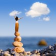 Woman and balanced stones on the sea — Stock Photo #9251413
