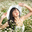 Young happy girl in the camomile field — Stock Photo