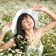 Young happy girl in the camomile field - Stock Photo