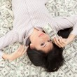 Young business woman resting upon money — Stock Photo