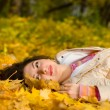 Young pretty woman on the autumn leaf — Stock Photo #9253477