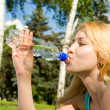 Pretty woman drinking water on the summer glade - Photo
