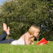 Young blonde reads book in the park - Foto de Stock