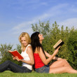 Young women read book in the park — Stock Photo