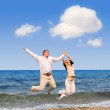 Happy young couple is jumping in the beach — Stock Photo #9255891
