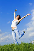 Expressive woman dancing on green grass — Stock Photo