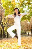 Pretty woman doing yoga exercises in the autumn park — Stock Photo
